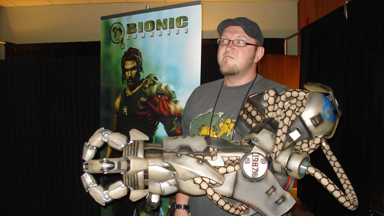 E3 2008: Für jeden Spaß zu haben, Paul posiert am Capcom Messe-Stand, damals noch im Dienste von 4Players, mit einem gigantischen bionischen Arm.